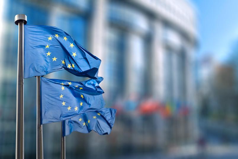 Flaggen der Europäischen Union wehen vor einem Gebäude.