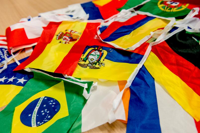 Verschiedene Flaggen liegen übereinander auf einem Tisch