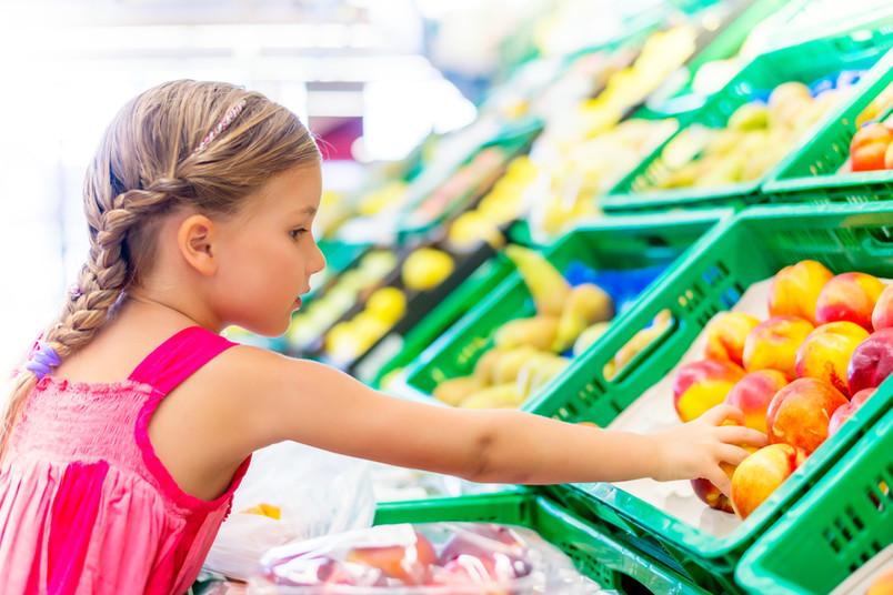 Ein Mädchen greift im Supermarkt zu gesundem Obst.