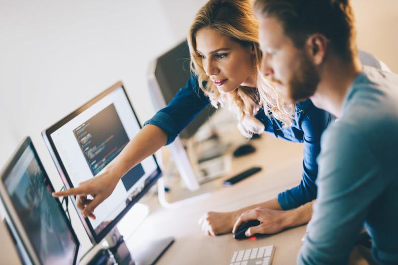 Junge Frau zeigt jungem Mann etwas am Bildschirm – es geht um Softwareentwicklung.