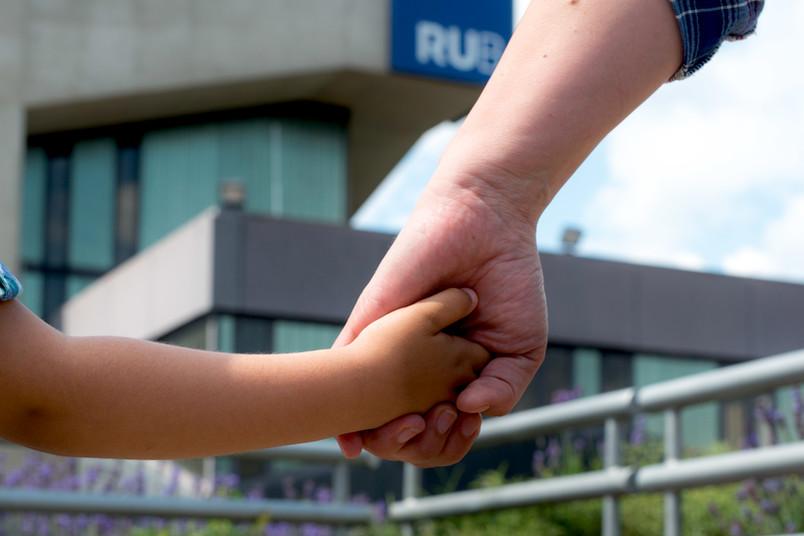 Kinderhand und Erwachsenenhand vor dem Musischen Zentrum der RUB