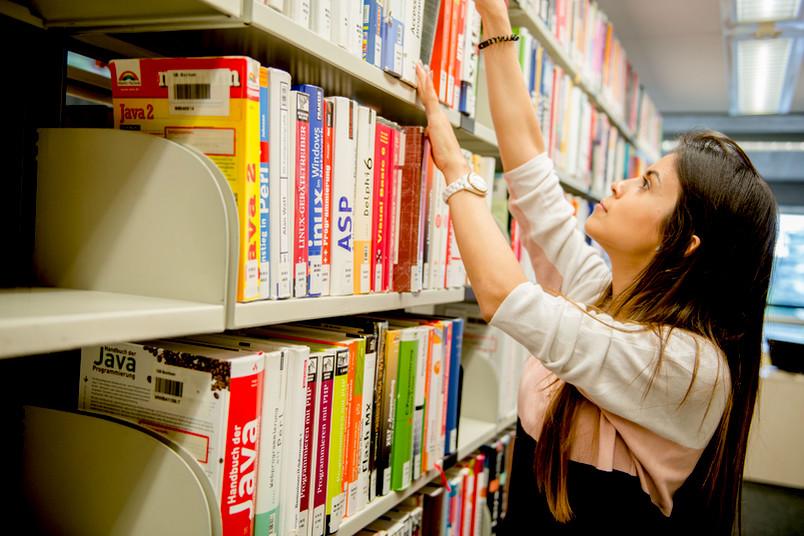 Studentin holt Buch aus Regal