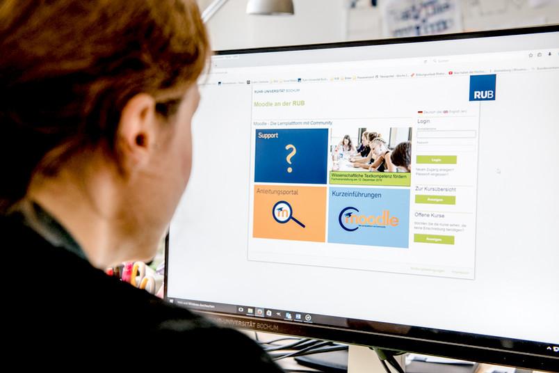Frau sitzt an einem Computerbildschirm.