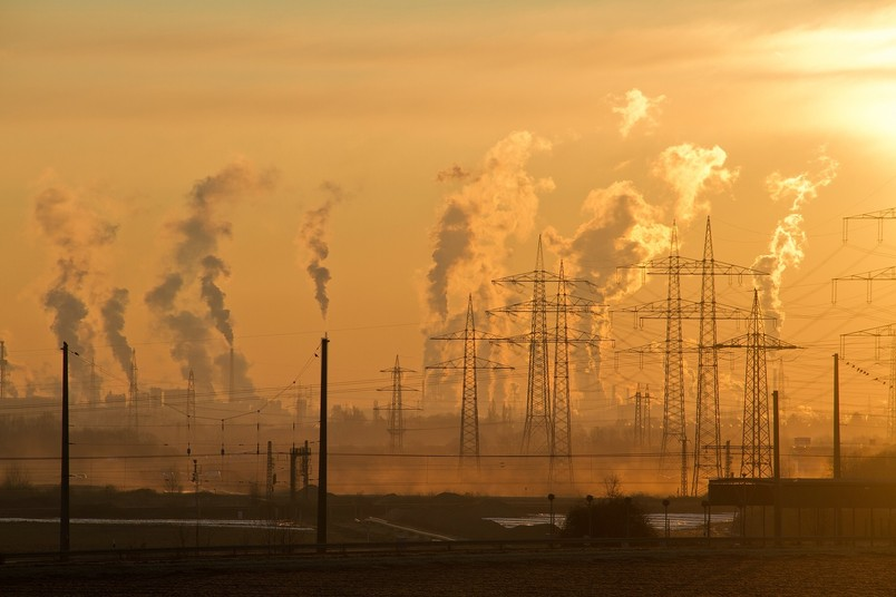 Stromleitungen und rauchende Industrieschornsteine im Sonnenuntergang