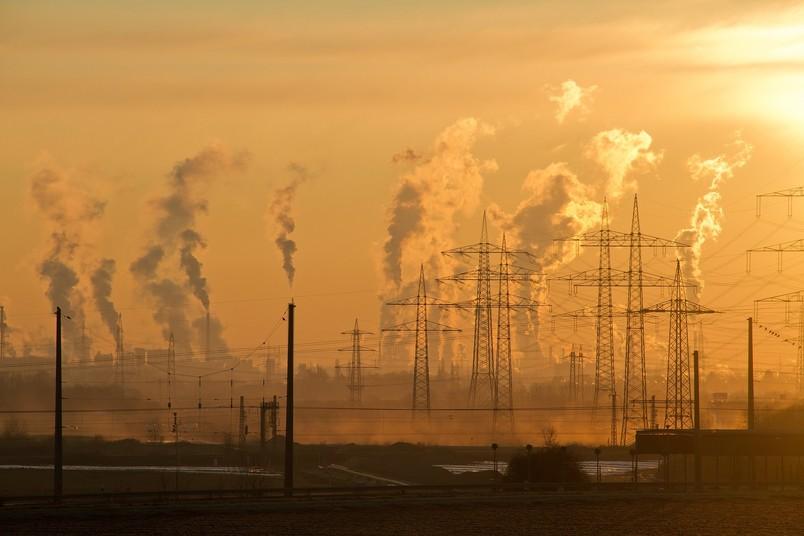 Rauchende Industrieschlote im Sonnenuntergang