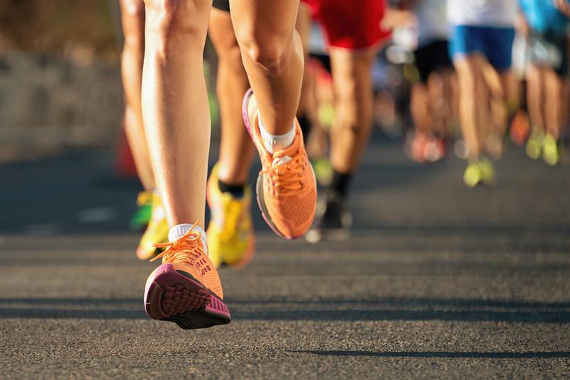 Beine und Schuhe von einer Gruppe Läufern in der Abendsonne