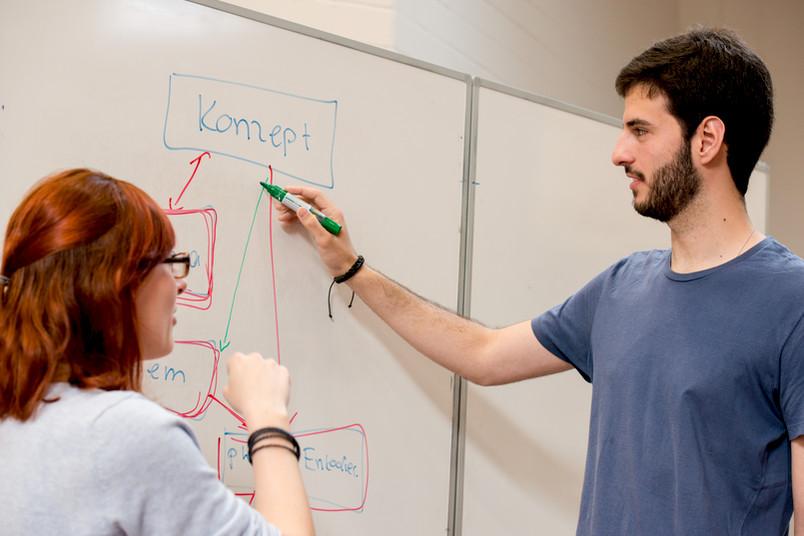 Dozentin und Student am Flipchart im Seminarraum