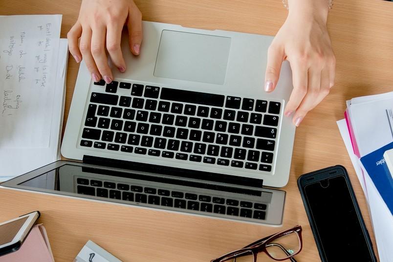 Hände tippen auf einem Laptop