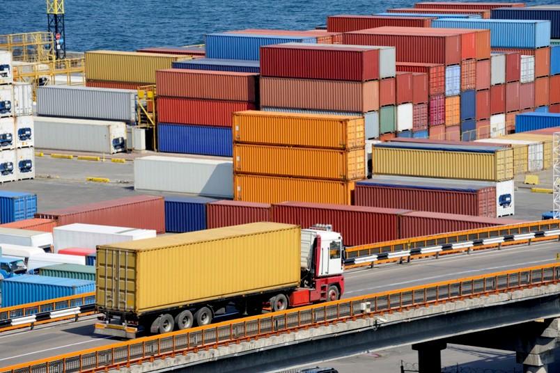 Container im Hafen, davor ein LKW auf der Straße