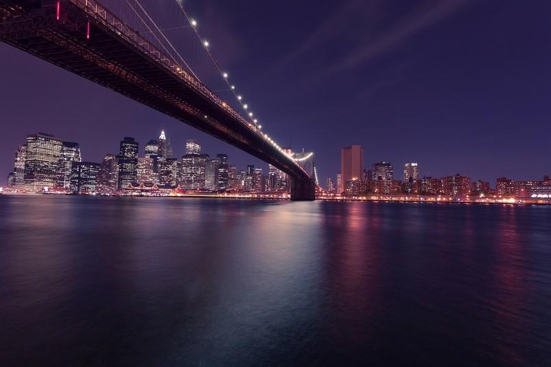 Skyline von New York City bei Nacht – im Vordergrund die markante Brooklyn Bridge