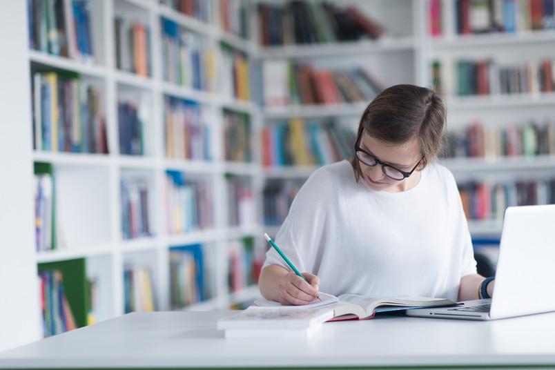 Frau mit Laptop und Büchern macht Notizen in einer Bibliothek