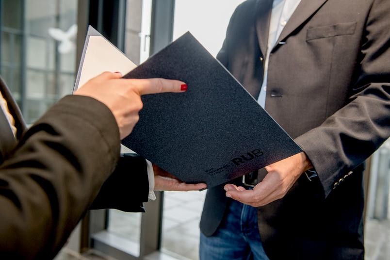 Urkundenübergabe, zu sehen sind Hände sowie die Urkunde