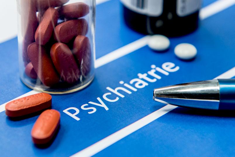 """Tabletten auf einem Zettel mit der Aufschrift """"Psychiatrie"""""""