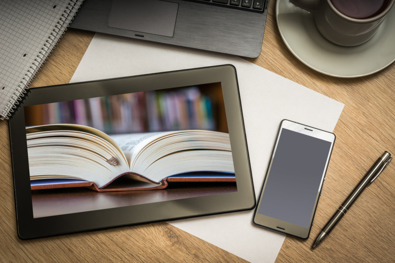Ein aufgeschlagenes Buch ist auf dem Bildschrim eines Tabletcomputers zu sehen.