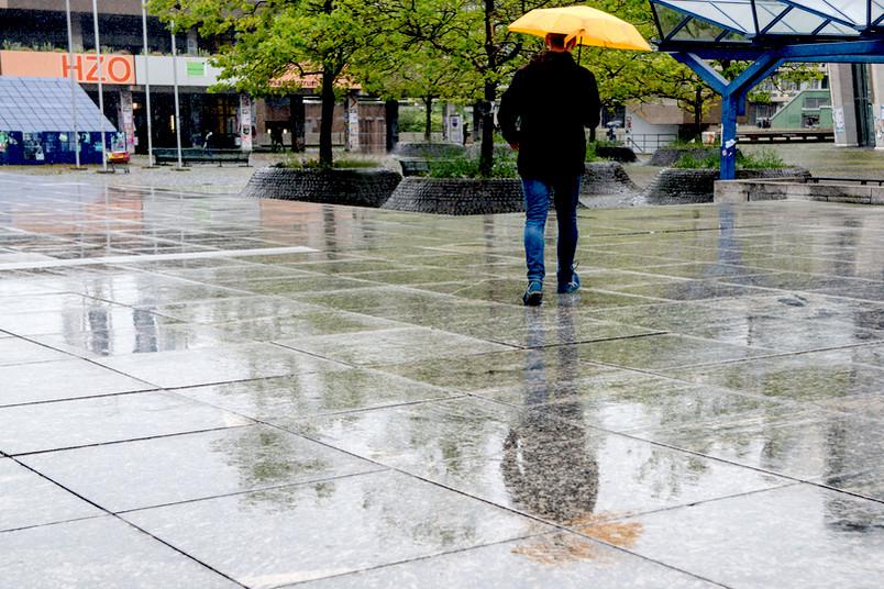 Mann mit gelben Regenschirm