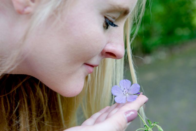 Frau riecht an Blume