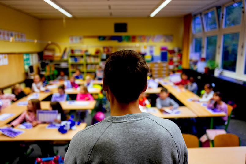 Lehrer steht vor einer Klasse.