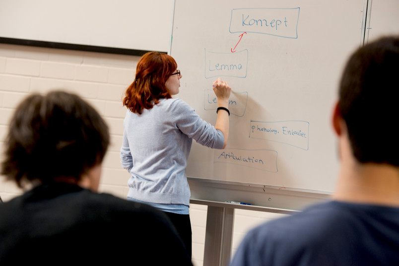 Eine Studentin steht an der Tafel, zwei Studenten sehen ihr zu
