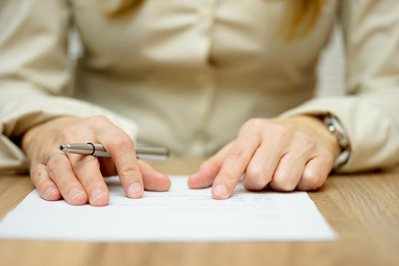 Situation in einer Sitzung: Frau mit Papier und Kugelschreiber in den Händen