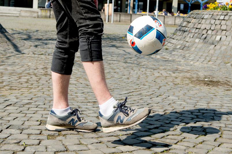 Mensch kickt Fußball in die Luft.