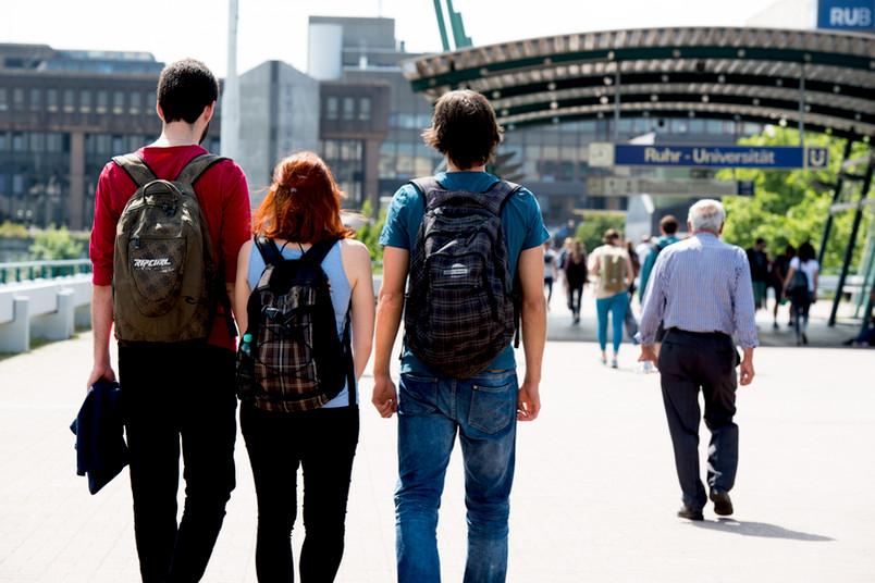Rückenansicht von drei Studenten auf dem Weg zur RUB.