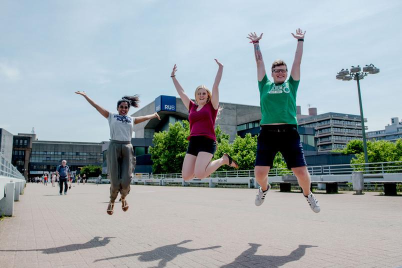 Studierende springen in die Luft.