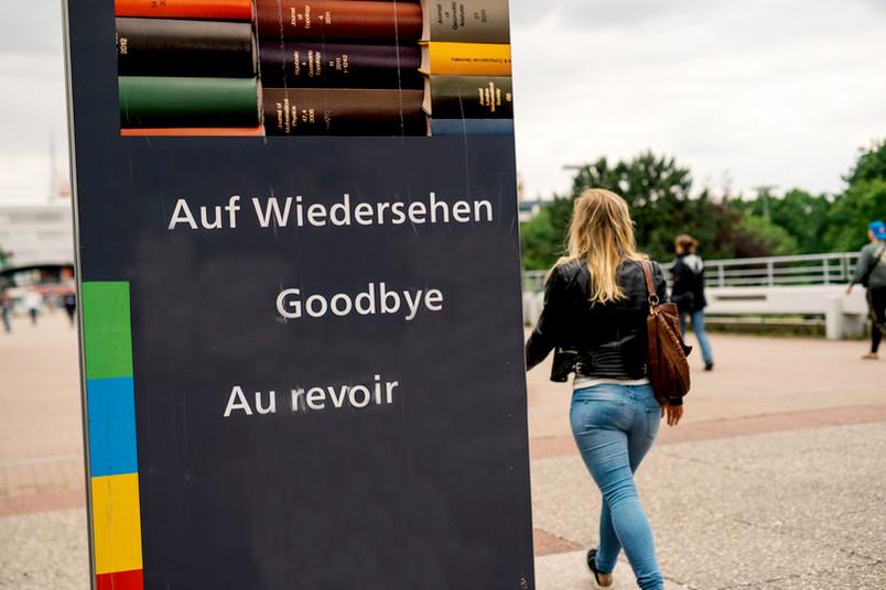 Studentin geht an einem Goodbye-Schild vorbei.
