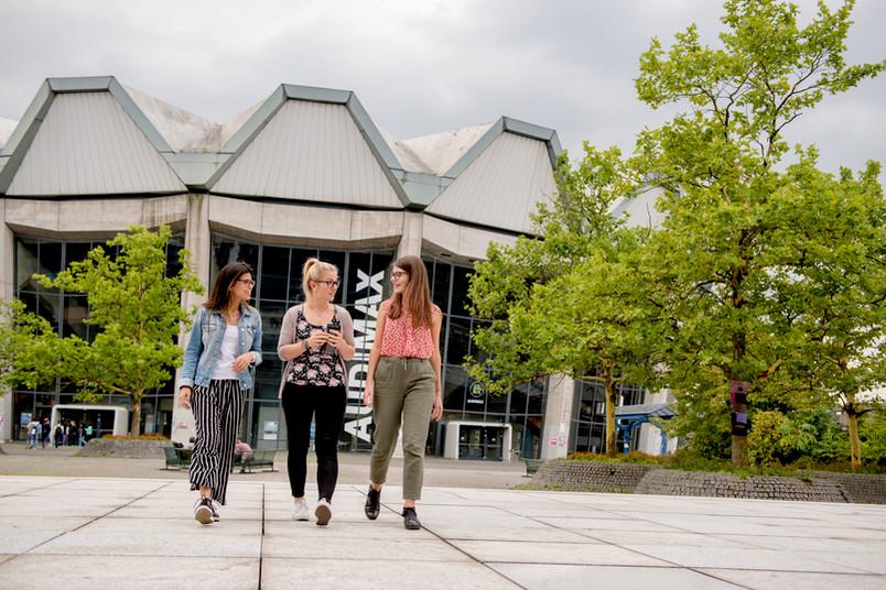 Studentinnen gehen über den Campus.