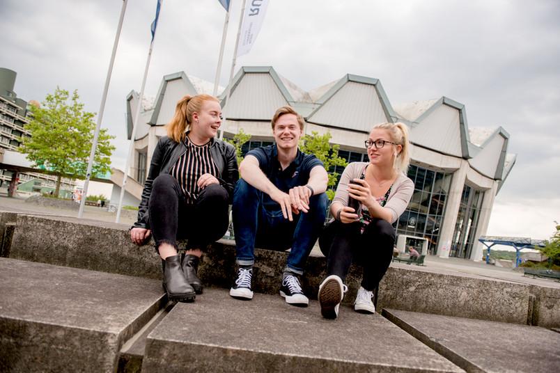 Studierende sitzen vor dem Audimax.