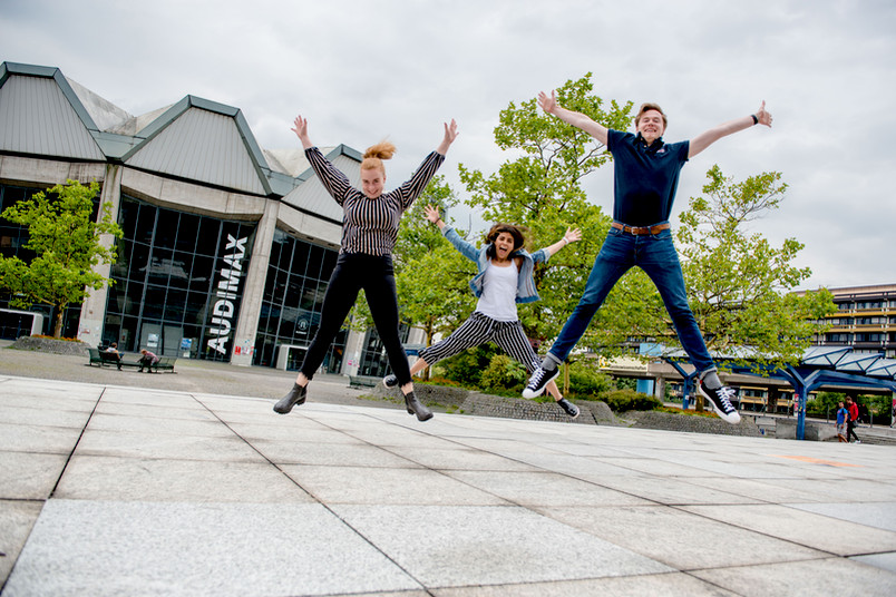 Semesterbeginn: Drei Studierende springen vor dem Audimax freudig in die Höhe