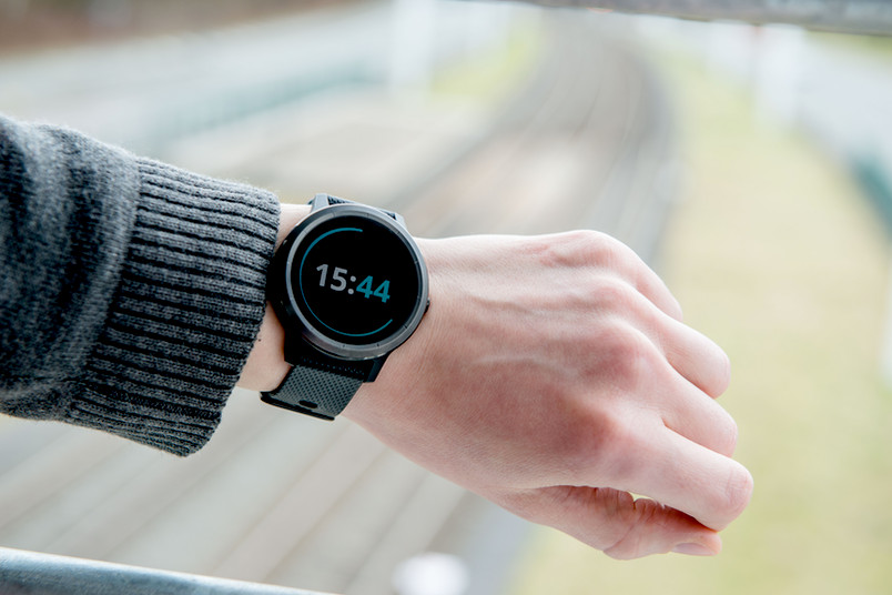 Eine Uhr im Vordergrund und Bahngleise im Hintergrund