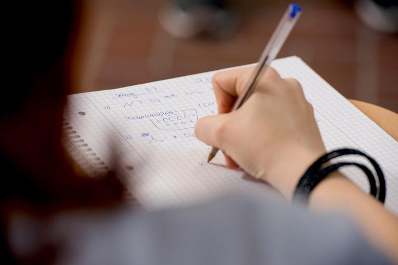Eine Hand, die mit Kuli Formeln auf einem Collegeblock notiert