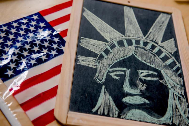 US-Flagge und Tafel mit Freiheitsstatue