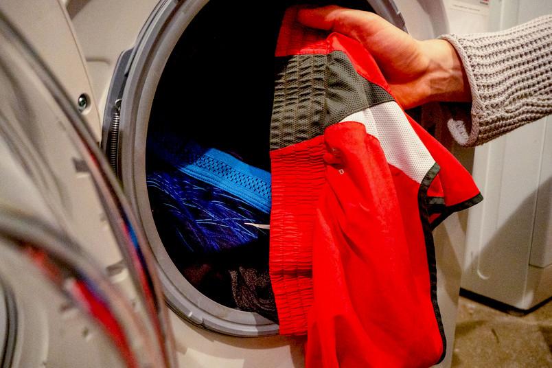 Sportwäsche wird in eine Waschmaschine gepackt.