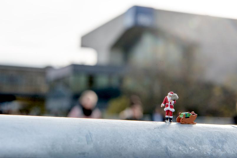 Mini-Weihnachtsmann auf der Unibrücke mit Campus im Hintergrund