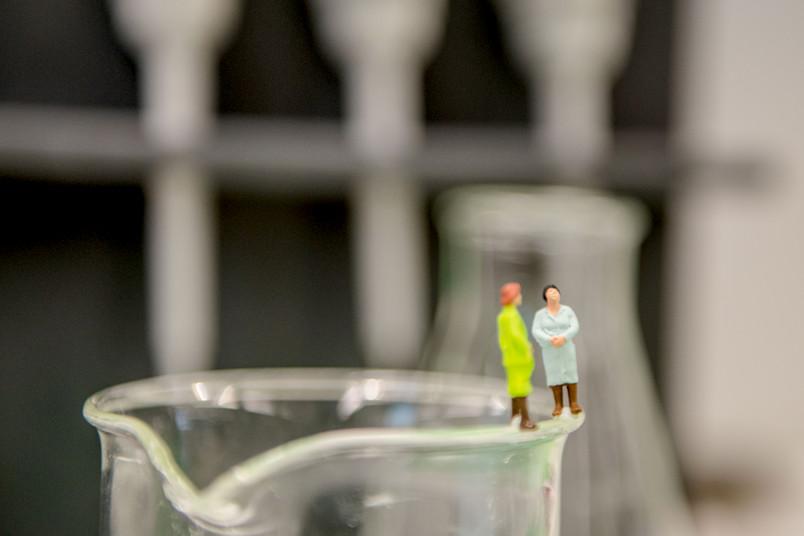 Zwei Minifiguren auf dem Rand eines Becherglases