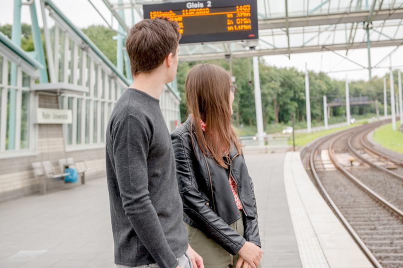 Studierende warten auf die Bahn.