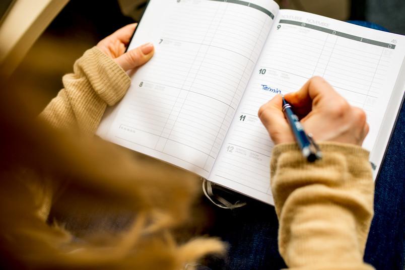 Frau trägt etwas in einen Kalender ein