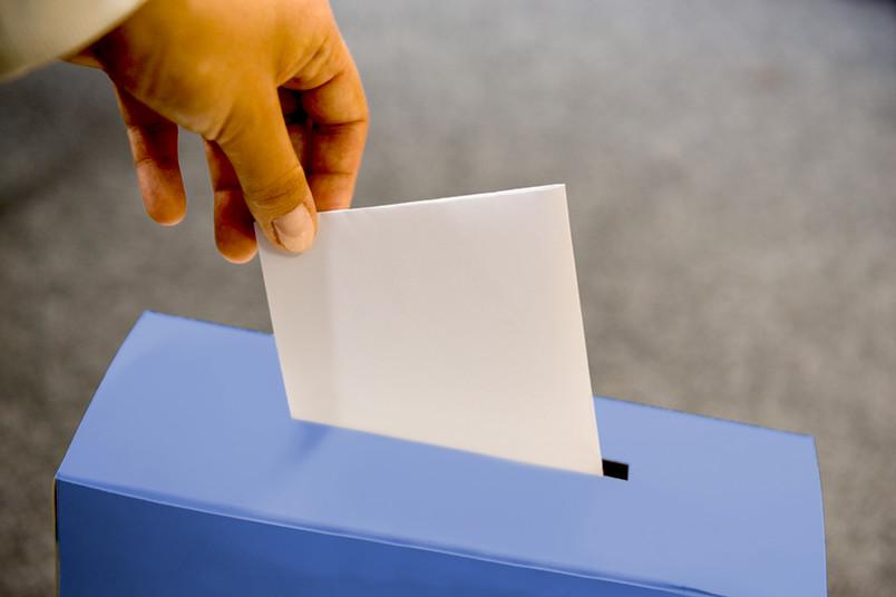 Eine Person steckt einen Wahlzettel in eine Urne.