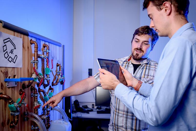 Forscher mit Tablet vor hydraulischem Versuchsstand