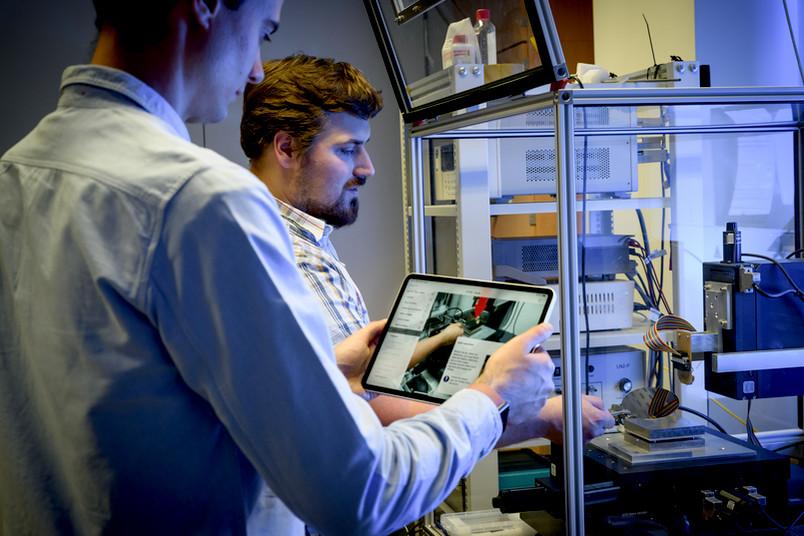 Forscher mit Tablet an Versuchsstand